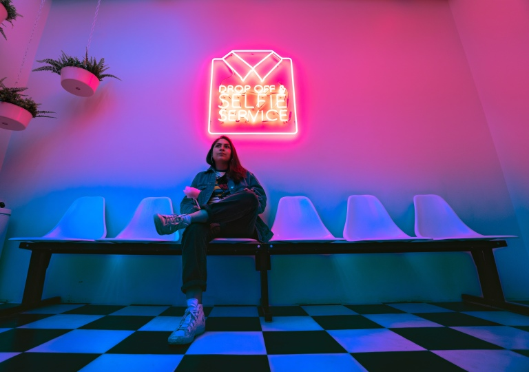 Woman sitting on seats under neon sign